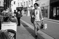He's looking Dapper (Howie Mudge LRPS) Tags: road street uk travel windows portrait people urban blackandwhite bw woman signs man male travelling monochrome wales architecture female buildings walking asian outside outdoors mono blackwhite student doors pavement walk candid pipes cymru bangor streetphotography streetlife monochromatic panasonic shops casual gwynedd urbanphotography northwales walles micro43 microfourthirds mirrorlesscamera compactsystemcamera lumixgvario1442f3556ii micro43mountlenses panasonicdmcgx8