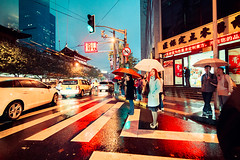Crossing Through The Rain (Jon Siegel) Tags: china people woman men wet girl beautiful rain night reflections walking lights evening lowlight nikon crossing shanghai traffic chinese pedestrians 28 umbrellas raining 14mm standingout samyang d810 samyang14mm samyang14mmultrawideanglef28ifedumc