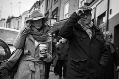 In Sync (Cliff.j) Tags: road street city winter people man cold london coffee hat lady zeiss scarf walking outside holding couple dof wind candid sony together cap carl sync portobello gesture unposed a7 gust mirrorless