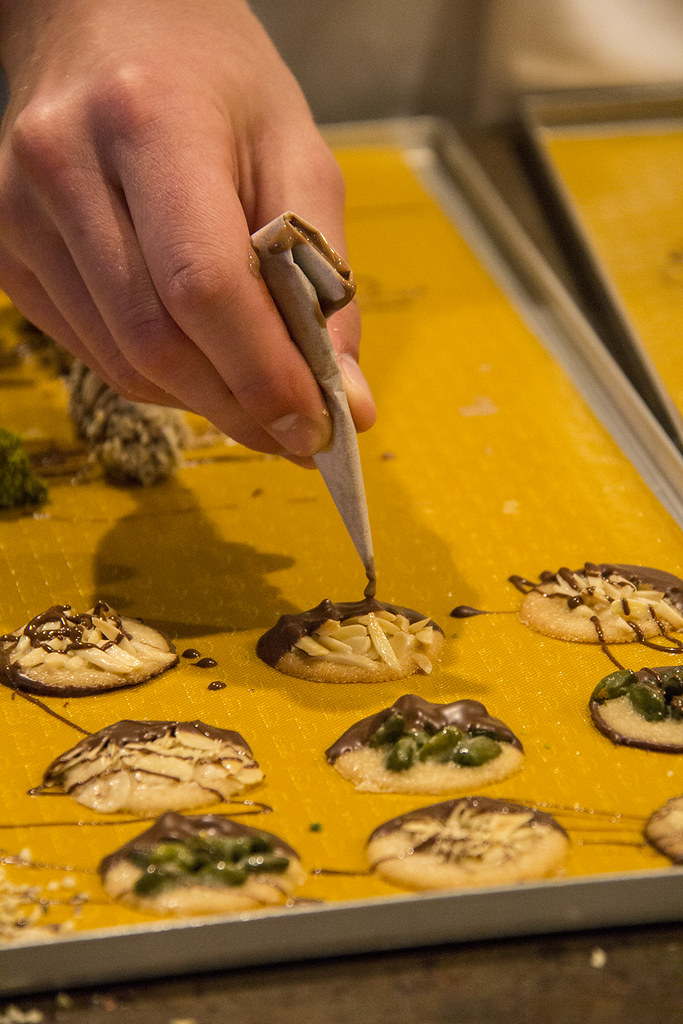 Fazendo biscoito na Kambly - mão colocando chocolate sobre a bolacha caramelizada