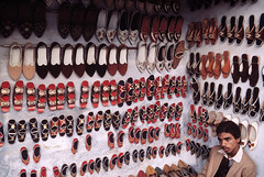 ouilavie: Bruno Barbey. India. Rajasthan. Pushkar fair. 1986. A shoe store in Pushkar. (johdahn) Tags: shop shoe magasin faces interior souvenir selling processed rajasthan intrieur alignment alignement chaussure babouche vendeur wallinside man18to25years asiansouthasianorigin homme1825ans asiatiquedelasiedusud murlintrieurdunbtiment
