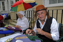 100905.164. Lace Maker.  (THDS050910addington-9.) (actionsnaps) Tags: uk family woman man male history female umbrella table fun glasses kent sitting market outdoor lifestyle craft streetscene pins sunshade pillow dressingup bowlerhat leisure bonnet adults spectacles derby bobbinlace waistcoat openair skill ramsgate bobbins dexterity thanet publicevent addingtonstreet costumedcharacter communityevent lacemaking mobcap victoriandress lacemaker landscapeformat horizontalimage gingerwig mopcap historicalfair maidscap