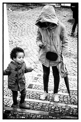 Young mother with cell and child close by (kirilko) Tags: people bw portugal umbrella canon pessoas gente lisboa lisbon streetphotography streetphoto paraguas pretoebranco calada candidshot guardachuva candidphoto enblancoynegro canoneos5d canonef24105mmf4lisusm fotocandid fotocndida skancheli photorua