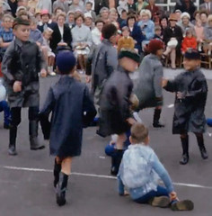 A wet day for play (theirhistory) Tags: school girls summer england film boys hat rain playground shirt kids children cap junior gb trousers shorts raincoat wellies primary rubberboots