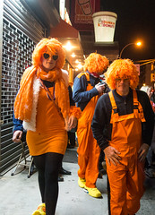 The Oranges (UrbanphotoZ) Tags: nyc newyorkcity orange woman ny newyork men halloween scarf grate downtown manhattan tshirt wigs westside blackshirt halloweenparade canalst jumpsuit dunkindonuts yellowsneakers heartshapedglasses