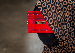 a bandari woman wearing a traditional mask called the burqa at panjshambe bazar thursday market, Hormozgan, Minab, Iran (Eric Lafforgue) Tags: red people woman horizontal closeup outdoors persian clothing asia veil mask iran muslim islam religion hijab culture persia headshot hidden covered iranian bazaar adults adultsonly oneperson traditionaldress burqa customs ethnicity middleeastern sunni burka chador balouch hormozgan onewomanonly burqua  bandari  embroidering 1people  iro thursdaymarket  minab unrecognizableperson colourpicture  borqe panjshambebazar iran034i2637 boregheh