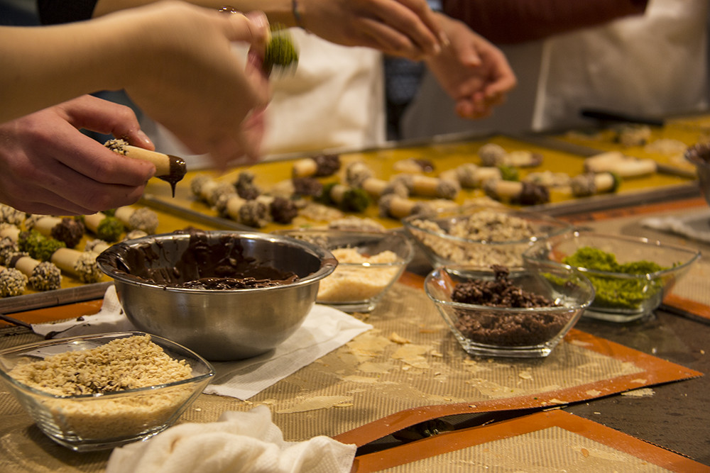 Fazendo biscoito na Kambly - mão passando chocolate nos canudos de bolacha