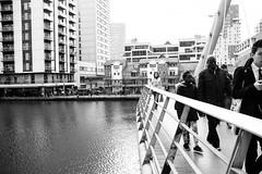 South Quay footbridge (lorenzoviolone) Tags: bridge england blackandwhite bw london monochrome architecture walking canal blackwhite unitedkingdom strangers streetphotography finepix fujifilm streetphoto canarywharf southdock fav10 agfascala200 mirrorless vsco southquayfootbridge streetphotobw vscofilm fujix100s x100s fujifilmx100s travel:uk=londonapr16
