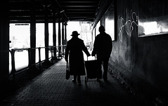 Need a Helping Hand | Day 188 / 365 (marcin baran) Tags: street old city bridge light shadow people urban woman man hat silhouette dark bag underpass walking holding couple fuji hand darkness walk trolley candid pair streetphotography poland polska tunnel sidewalk help human older fujifilm streetphoto 365 passage factor hold element helping gliwice candidphotography x100 365project marcinbaran x100t