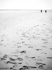 Distant (Dell's Pics) Tags: people bw white black beach wales walking mono couple footprints away olympus monotone portmeirion distance omd em5
