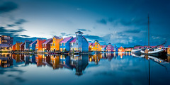 Colorful Houses during blue hour (revisited) (Maarten Mensink.com) Tags: city travel blue houses light sunset sky urban panorama lake color colour reflection water netherlands architecture night clouds reflections landscape landscapes boat colorful pano nederland houseboat wideangle panoramic hour bluehour colourful groningen reitdiep ultrawideangle reitdiephaven