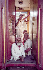 Men On Train In India (Peter Davidson Hendley) Tags: old city travel light sea vacation sky people urban woman india house lake holiday color building tree men history film tourism nature water beautiful beauty vertical horizontal wall architecture sunrise 35mm river relax landscape boats outdoors hotel boat dock eyecontact asia ship view place image indian south traditional famous transport group houseboat oldman vessel landmark tourist historic holy exotic tropical romantic recreation staring handicapped dhoti ganges varanassi 3men crowdofpeople legless navigable 1boy traintransportation