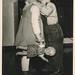 Little boy kissing a girl holding a doll
