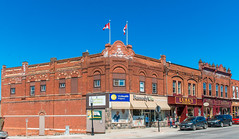 Queen Street (fotofrysk) Tags: blue red sky ontario canada building cars town bricks flags storefronts queenstreet centurybuilding durhamregion canadianflags portperry nikond7100 perrystreetsmalltownontario 201604174049