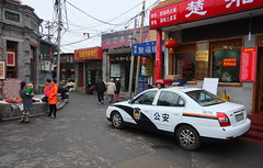 "China Beijing hutong backalley with parked police cruiser - ""Blue n White (sorta)"" (moreska) Tags: china city urban car facade asia backalley candid beijing police kingdom voiture wires alleyway storefront carro vehicle shield hutong middle hanja logos cruiser siren lawenforcement streetview unstaged hepingman"