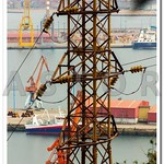 Old and rusty electrical tower with a boat in the background thumbnail