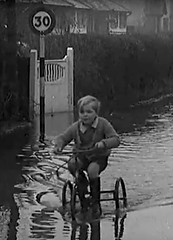 Done for speeding (theirhistory) Tags: road street boy water kid village child flood pavement path tricycle jumper trike shorts speedlimit wellies wellingtoms