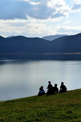 Silhouettes of a family staring at the lake by ioanna papanikolaou DSC_1305_1991 (joanna papanikolaou) Tags: family people lake mountains green nature water grass clouds scenery sitting view dusk horizon hill scenic silhouettes scene environment waterscape lakescape lakescenery