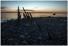 Unforgiving waters (Hugh Stanton) Tags: sunrise boat pebbles shore wreck groins