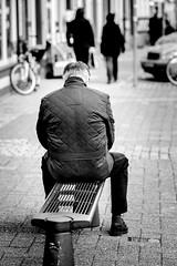 Straddling the Bench (Mister G.C.) Tags: life street city people urban blackandwhite bw man male guy monochrome germany bench lens deutschland photography prime nikon europe sitting shot image candid seat streetphotography 85mm photograph frombehind nikkor dslr unposed schwarzweiss straddling niedersachsen lowersaxony strassenfotografie d5300 85mmf18g strassenphotographie mistergc