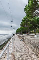 The Long Walk II (PuffinArt) Tags: bridge trees winter portugal wet water clouds river nikon rocks lisboa lisbon sidewalk cablecar handrail puffinart nikkor guardrail hdr vr parquedasnaes darksky d300 revetment 18200mm vandamalvig stonefacing