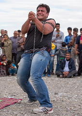a strongman struggles to break free of chains at the panjshambe bazar thursday market, Hormozgan, Minab, Iran (Eric Lafforgue) Tags: show people men public vertical rural outdoors chains pain women asia power iran audience market circus muslim crowd performance culture persia scene entertainment strong marketplace strength iranian perform bazaar performers performer groupofpeople unexpected extraordinary abnormal physical middleeastern strongman uncommon hormozgan   5people  iro  minab colourpicture  panjshambebazar iran034i3171