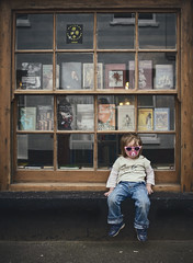 Sitting Pretty. (markfly1) Tags: uk pink blue england window sunglasses shop kids 35mm children book cool nikon sitting norfolk large down books sash jeans d750 dummy pacifier
