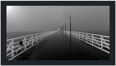 schorncliffe pier in the rain 2. (agphoto100) Tags: ocean wood sky white black wet rain mono pier fuji timber jetty border gray rail sae brisbane finepix frame queensland lamps railing posts sandgate f770exr