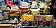 Eastern, Western and Cowboy hats (Tex Texin) Tags: shop booth cowboy colorful crafts muslim prayer middleeast hats straw souk vendor oman seller muscat muttrah mutra