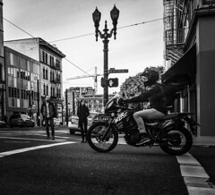 Urban Two-Wheeling (TMimages PDX) Tags: road street city people urban blackandwhite monochrome buildings portland geotagged photography photo traffic image streetphotography streetscene sidewalk photograph transportation pedestrians pacificnorthwest avenue fineartphotography mortorcycle iphoneography