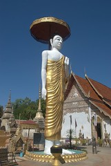 Standing Buddha with temple in background (VinayakH) Tags: thailand temple buddha stupa buddhist buddhism phrae watphrathatchomchaeng