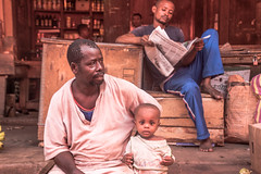 the daily news in africa (bocero1977) Tags: africa street blue light people man colors shop newspaper child market outdoor fineart barefoot zanzibar moment