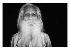 the bearded wise man (handheld-films) Tags: travel portrait people blackandwhite india man male monochrome closeup beard intense faces serious indian formal documentary sombre elderly portraiture wise wisdom bearded direct guru whitebeard longbeard