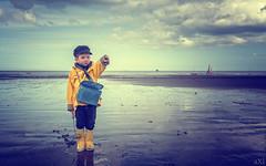 The boy in the yellow raincoat (Axel Steinars.) Tags: boy beach yellow jaune children raincoat plage garon impermable manteaudepluie