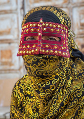 a bandari woman wearing the traditional mask called the burqa on a market, Hormozgan, Bandar Abbas, Iran (Eric Lafforgue) Tags: portrait people woman vertical outdoors gold golden persian clothing asia veil mask iran market muslim islam religion hijab persia headshot hidden covered iranian bazaar adults adultsonly oneperson islamic burqa ethnicity middleeastern frontview persiangulf sunni bandarabbas burka chador 20sadult youngadultwoman balouch hormozgan onewomanonly lookingatcamera burqua   embroidering 1people  iro straitofhormuz  colourpicture  borqe boregheh iran034i1980