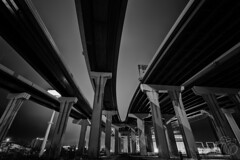 Arteries of Motion (CJ Schmit) Tags: road longexposure nightphotography winter sky urban blackandwhite bw snow cold monochrome wisconsin canon concrete lowlight highway downtown transportation freeway milwaukee underneath pillars converge i94 mke shutterdrag i43 marquetteinterchange canonef1740mmf40lusm highrisebridge canon5dmarkiii cjschmit 5dmarkiii wwwcjschmitcom niksilverefex2 cjschmitphotography
