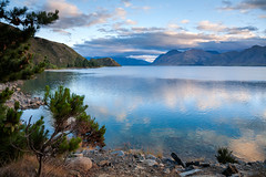 Sunrise over Lake Hawea in New Zealand (Dmitri Naumov) Tags: blue newzealand summer sky mountain lake tree nature water horizontal pinetree rural landscape outdoors photography coast pond quiet view cloudy vibrant atmosphere nobody nopeople calm clear shore lakeshore otago environment remote idyllic ambience climate tranquil waterside scenics hawea distant 2010 waterscape mountainrange morming traveldestinations colorimage moodysky reflectioninwater beautyinnature nonurban southislandnewzealand sunrisedawn