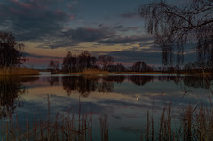 The charm of nightfall (piotrekfil) Tags: trees sunset sky moon lake nature water clouds reflections dark landscape twilight pentax dusk poland moonrise waterscape piotrfil