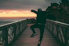 jump on the darkside. (daynmoron) Tags: ocean bridge sunset sea sky sun mer man france night clouds landscape alone photographer paysage biarritz videographer