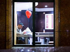 You Will Know Me By the Red Balloon    Day 245 /365 (marcin baran) Tags: street city red people urban man color window person restaurant newspaper alone sitting fuji heart pov perspective streetphotography poland polska human fujifilm lonely mcdonald gliwice x100 lonelu marcinbaran x100t