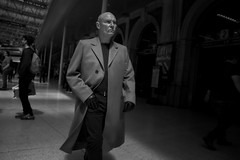 Just Business. (Places, Faces) Tags: city travel light england people urban blackandwhite bw man london monochrome look smart station leather walking mono shadows britain candid centre central illuminated professional gloves capture stern peoplewatching overcoat attire urbanstreets candidcapture meanlookin robmchale