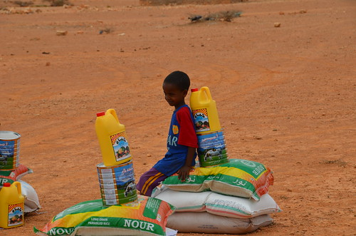 A child with newly-received food provisions in drought-hit Puntland