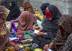 a bandari woman wearing a traditional mask called the burqa at panjshambe bazar thursday market, Hormozgan, Minab, Iran (Eric Lafforgue) Tags: people face horizontal outdoors persian clothing women asia veil mask iran market muslim islam religion hijab culture persia tribal hidden masks covered iranian bazaar adults groupofpeople adultsonly islamic traditionaldress burqa customs ethnicity middleeastern sunni burka chador balouch hormozgan burqua  bandari  5people embroidering  iro thursdaymarket  minab colourpicture  borqe panjshambe panjshambebazar boregheh iran034i2801