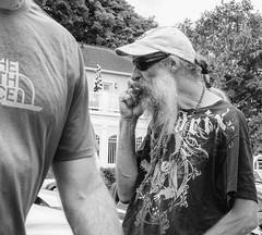 Bearded Hendrix Fan (J Wells S) Tags: blackandwhite bw monochrome sunglasses beard necklace thenorthface michigan cigar streetscene ponytail jimihendrix harborsprings hipshot streetshot beadednecklace braidedbeard