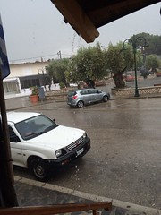 (Psinthos.Net) Tags: road trees storm tree cars water rain clouds drops spring cloudy pavement sidewalk pots april raindrops raining treebranches olivetrees paved cloudiness        psinthos