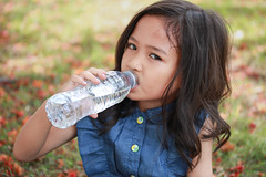 Asian little girl drinks mineral water. (diary of moon) Tags: summer portrait people baby white hot cold color cute green nature water girl beautiful beauty closeup female garden asian fun thailand happy person bottle healthy holding asia pretty child hand little drink outdoor head beverage young sunny bubbles clean plastic health thai heat mineral liquid thirsty freshness refreshment caucasian refresh