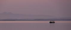 Dawn on the Bay (Dalliance with Light (Andy Farmer)) Tags: ocean sea sky mist seascape mountains water bicycle fog sunrise reflections landscape dawn bay boat haze cu cuba negativespace bluehour cienfuegos