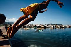 Diving Near Slums of Cebu City Philippines (AdamCohn) Tags: adamcohn cebu cebucity philippines ybanezcompound bridgejumping children diving fun jumping kids play playing shacks slum slums street swimming wwwadamcohncom