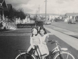 Little girl poses with her doll and bicycle