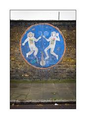 Community Art (?), East London, England. (Joseph O'Malley64) Tags: brick tarmac wall moss eva pavement space astronauts handpainted barbedwire algae outerspace plywood brickwork weightless spaceflight spacewalk flagstones woodenpanel granitekerbing
